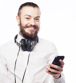Sorridenti giovane uomo barbuto con cellulare isolato su sfondo bianco