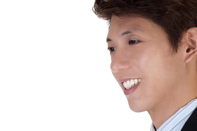 Fronte sorridente felice dell'uomo di affari del giovane, ritratto del primo piano con copyspace su bianco.