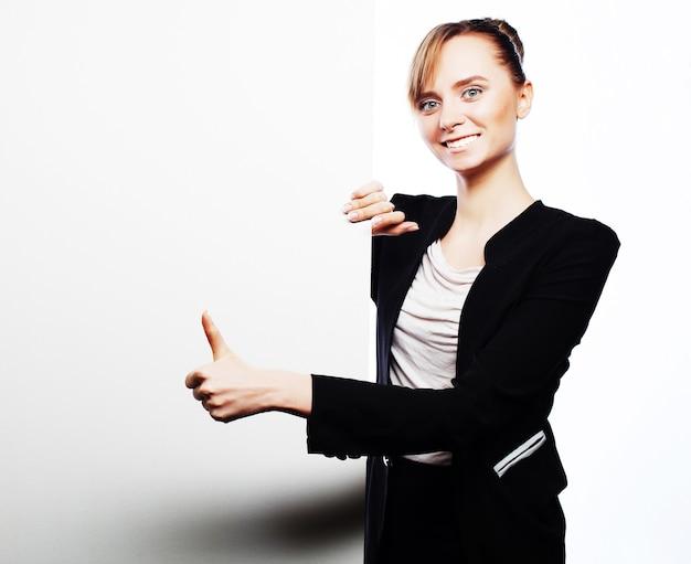 Sorridenti giovane donna d'affari che mostra cartello bianco, su sfondo bianco