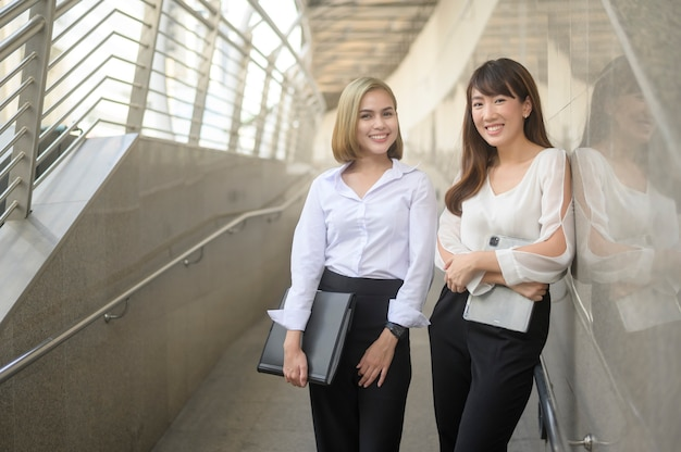 Giovani donne d'affari sorridenti felici stanno lavorando nella città moderna, parlando di business plan