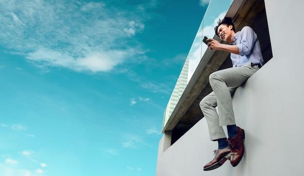 Felice sorridente giovane imprenditore in abbigliamento casual utilizzando il telefono cellulare sul tetto alto urban city sky. inquadratura dal basso