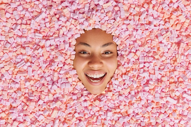 Sorridenti giovane donna etnica attacca la testa in gonfio appetitoso marshmallow sorrisi a trentadue denti si diverte mangia appetitoso gustoso dessert dolce di andare a preparare un pasto delizioso