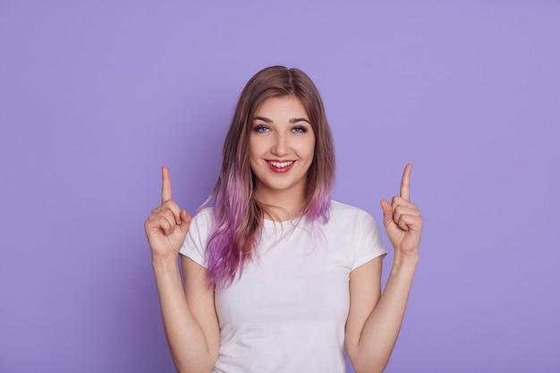 Giovane donna sorridente felice che indossa la maglietta casual bianca che punta entrambi gli indici verso l'alto, mostrando lo spazio libero per il testo della pubblicità o della promozione, isolato sopra il muro viola.