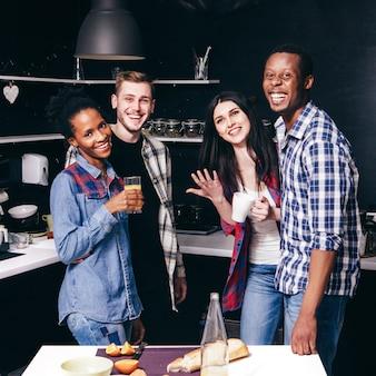 Giovani amici sorridenti felici in cucina, due coppie interrazziali vivono insieme