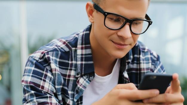 Giovane sorridente felice che per mezzo del dispositivo moderno dello smartphone