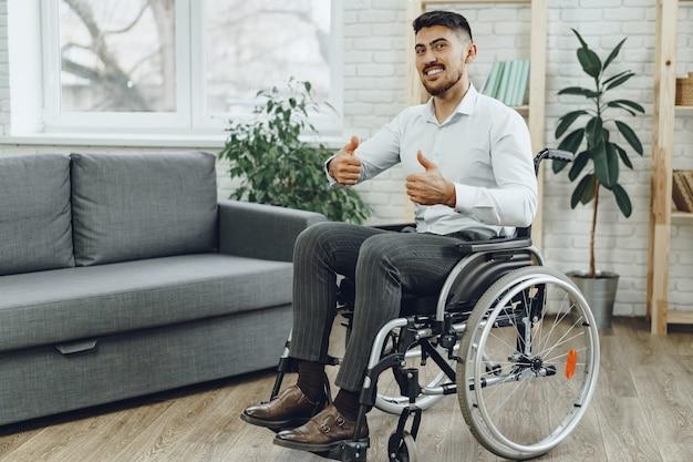 Giovane sorridente felice su una sedia a rotelle a casa