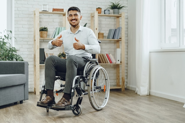 Felice sorridente giovane uomo in sedia a rotelle stare a casa