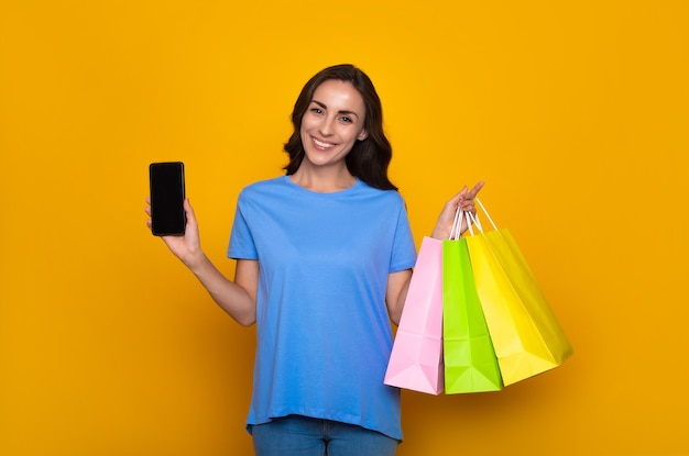 Una giovane donna sorridente felice in abiti casual con borse della spesa colorate mostra lo smartphone e posa su sfondo giallo