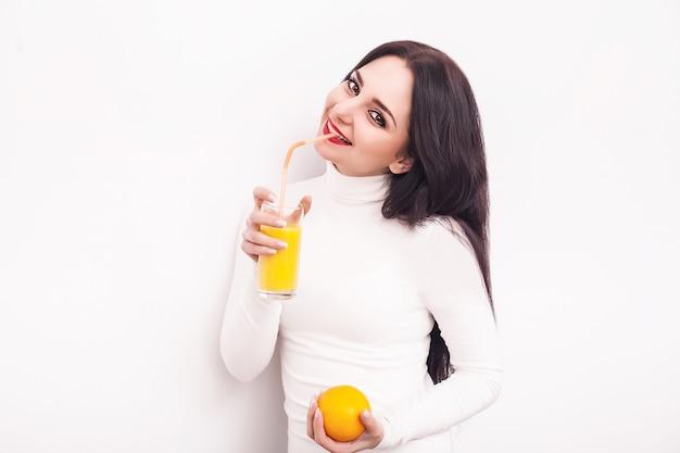 Giovane donna sorridente felice che beve il succo d'arancia