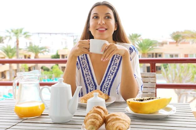 Giovane donna sorridente felice che mangia prima colazione nel suo hotel di villeggiatura
