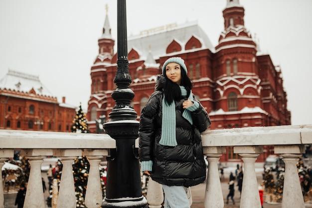 Giovane donna sorridente felice che posa nella piazza rossa, mosca