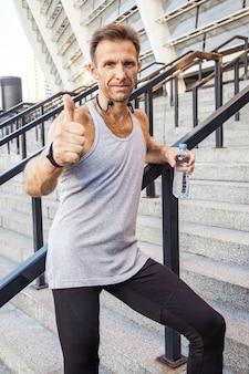 Felice sportivo sorridente che tiene in mano una bottiglia d'acqua in piedi sui gradini guardando la telecamera sorridendo e