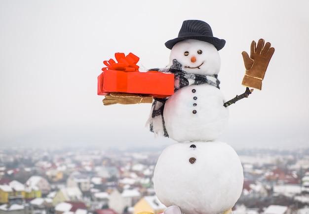 Pupazzo di neve felice con regalo agitando la mano pupazzo di neve con scatola regalo pupazzo di neve con cappello sciarpa guanti natale