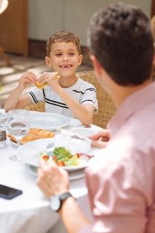 Figlio felice. piccolo figlio felice che mangia delizioso panino al pollo durante la colazione in famiglia fuori casa