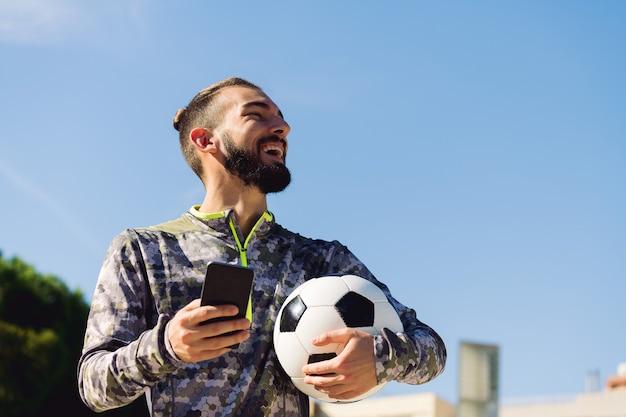 Sportivo felice che ride con il telefono in mano