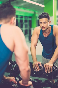 Lo sportivo felice si guarda allo specchio nel fitness club