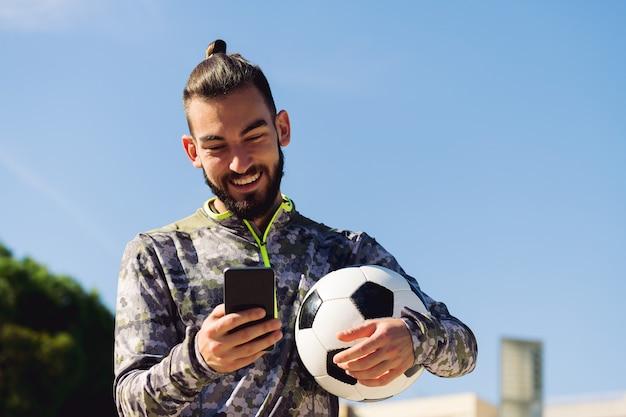 Felice sportivo sorridente guardando il suo telefono cellulare