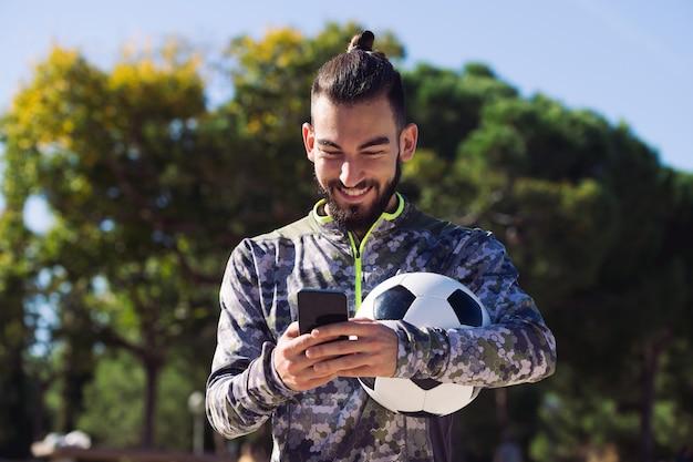 Sportivo felice che scrive un messaggio sul suo telefono