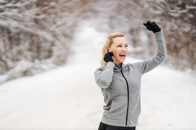 Sportiva felice che gode della musica e che prende una pausa dall'esercizio mentre levandosi in piedi nella natura al giorno di inverno nevoso