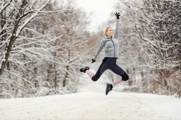 Felice sportiva che salta in alto nella natura al giorno di inverno nevoso.