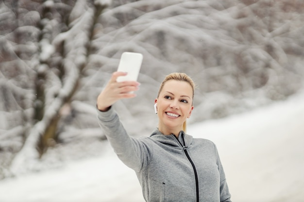 Felice sportiva in piedi nella natura al giorno di inverno nevoso e prendendo un selfie per i social media.