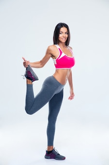 Felice donna sportiva che allunga la gamba