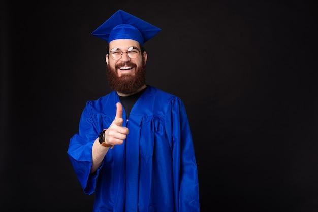 Felice studente uomo in scapolo che punta verso la telecamera