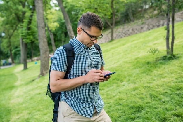 Studente felice che guarda video su smartphone in un parco