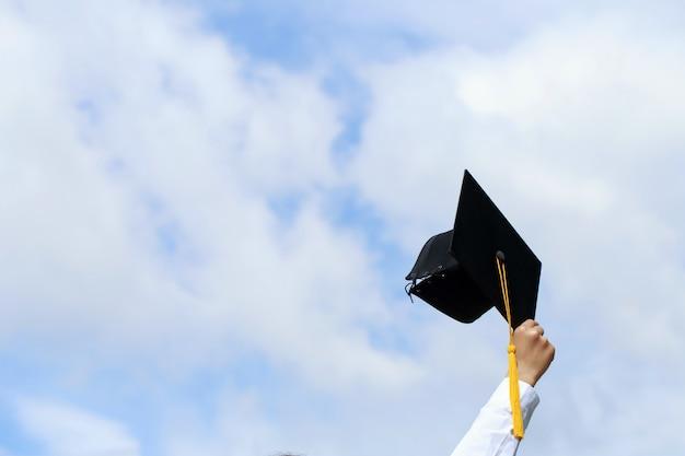 Studenti felici in abiti stanno celebrando la laurea alzando le mani in alto i cappelli di laurea in aria