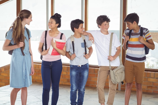 Studenti felici che interagiscono tra loro nel corridoio