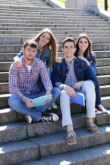 Studenti felici che si siedono sulle scale nel parco