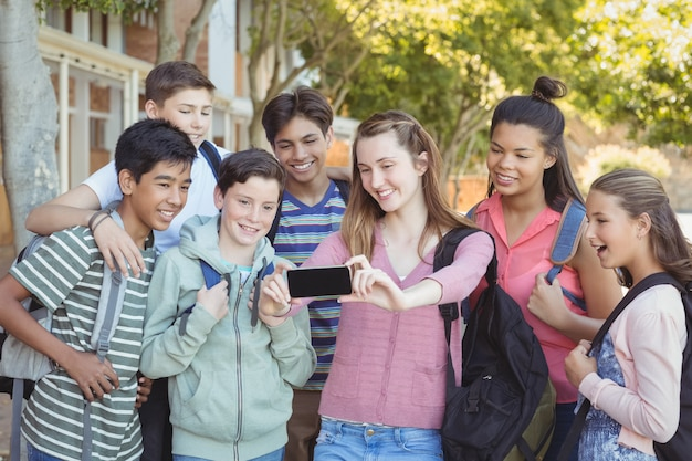 Studenti felici che prendono selfie sul cellulare nel campus