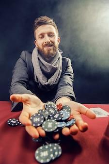Uomo barbuto elegante felice in vestito e sciarpa che giocano nel casinò scuro