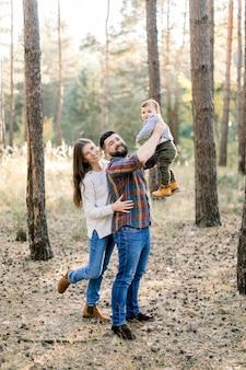 Famiglia felice ed elegante in abiti casual, papà, mamma e figlio piccolo stanno camminando nella foresta di autunno, divertendosi e giocando con il bambino