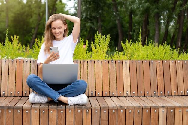 Felice blogger femminile alla moda che ride mentre chatta con gli amici nei social network sul dispositivo portatile. giovane donna che legge un piacevole messaggio di testo dal migliore amico connesso a internet pubblico all'aperto