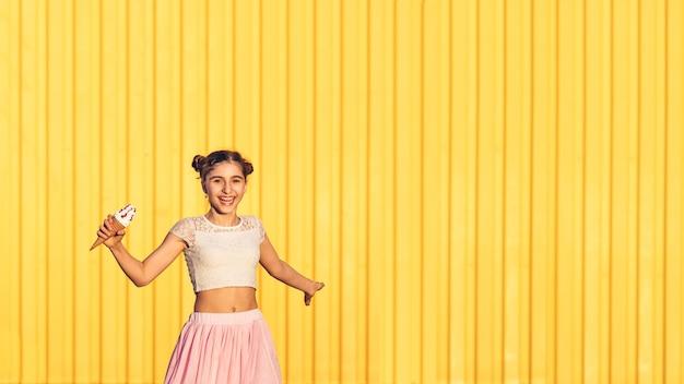 Felice ragazza alla moda in gonna rosa con gelato in mano e sorridente contro il muro giallo