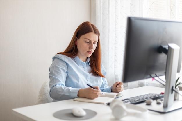 Felice donna elegante che lavora a distanza dall'ufficio a distanza di casa sul pc prendendo appunti sorridendo