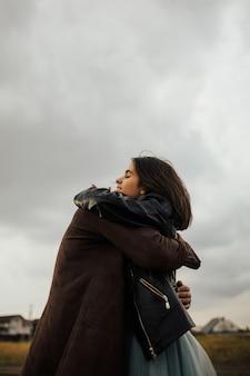 Felice coppia giovane alla moda abbracci e risate all'aperto.