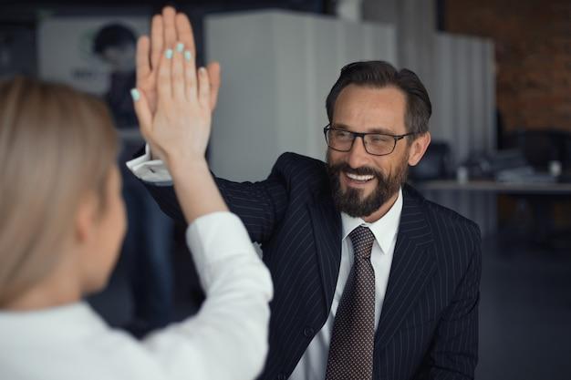 Uomo d'affari di successo felice che dà il cinque con la donna di affari che sta indietro nella priorità alta. concetto di lavoro di squadra.