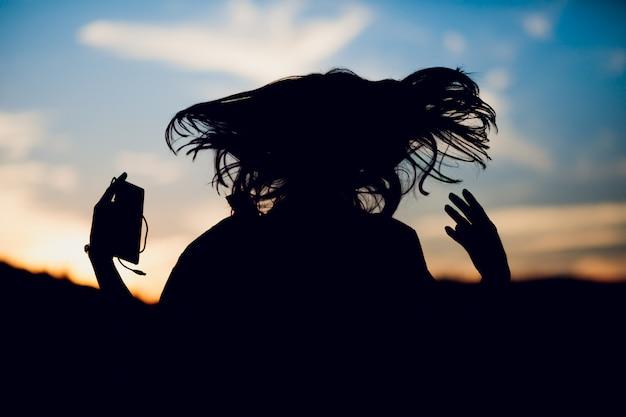 Sportiva di successo felice che alza le armi al cielo sull'estate di tramonto di illuminazione posteriore dorata. copia spazio.