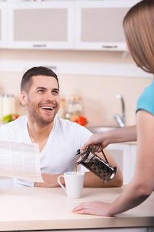 Buona domenica mattina. donna che versa il caffè nella tazza mentre un giovane felice tiene in mano il giornale e sorride