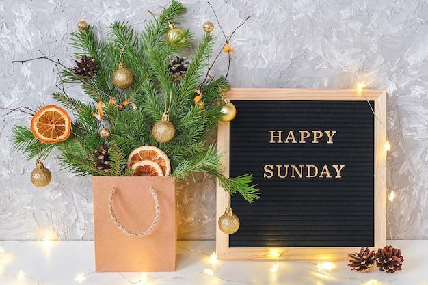 Testo di domenica felice sul bordo di lettera nero e mazzo festivo dei rami dell'abete con la decorazione di natale
