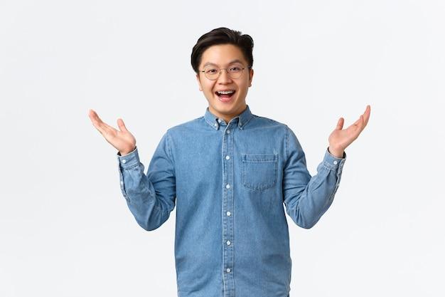 Felice uomo asiatico sorpreso con bretelle, indossando occhiali, benvenuto persona, sorridente amichevole e alzando le mani eccitato, riceve buone notizie, rallegrandosi o lodando qualcuno, in piedi sfondo bianco.