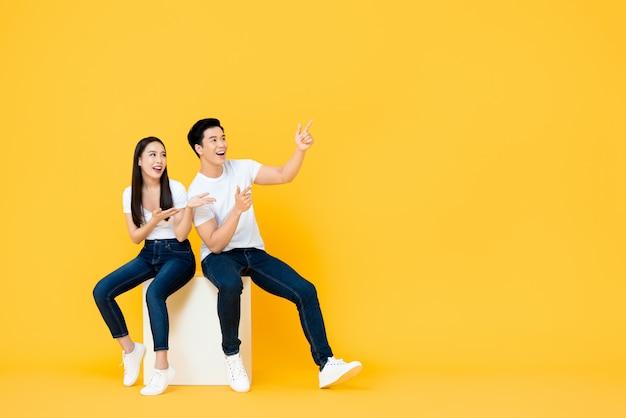 Le giovani coppie asiatiche attraenti sorprese felici che indicano e che esaminano lo spazio in bianco accanto in giallo hanno isolato la parete di stuidio