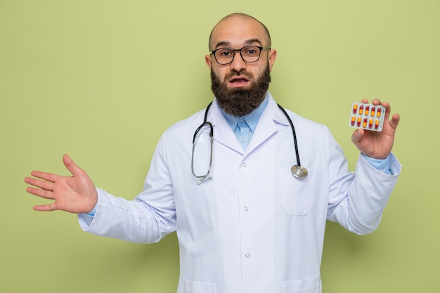 Felice e sorpreso uomo barbuto medico in camice bianco con uno stetoscopio intorno al collo con gli occhiali azienda blister con pillole sorridente allegramente con il braccio alzato