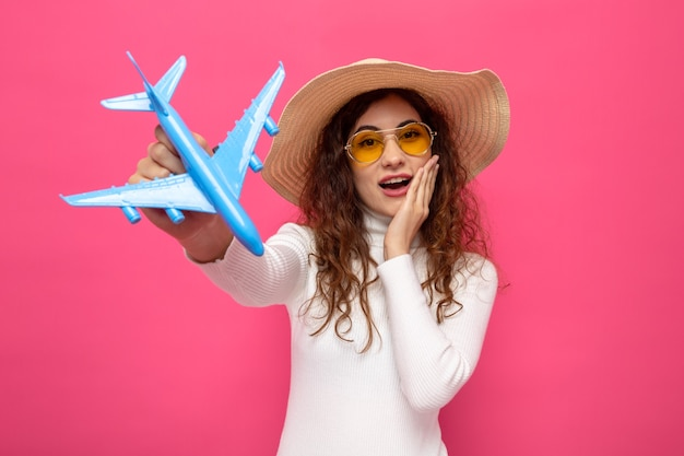 Felice e sorpresa giovane bella donna in dolcevita bianco che indossa occhiali gialli e cappello estivo che tiene aeroplano giocattolo guardando davanti sorridendo allegramente in piedi sul muro rosa