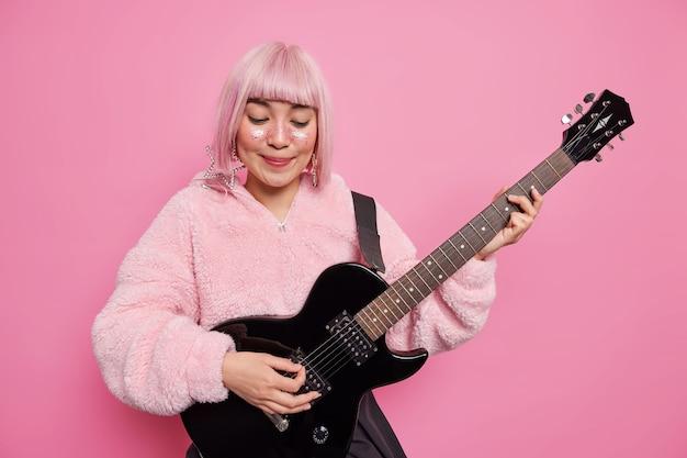 Felice musicista femminile di talento suona la chitarra elettrica si prepara per il concerto rock trascorre molto tempo in studio di registrazione ha luccichii sul viso vestito con una calda pelliccia