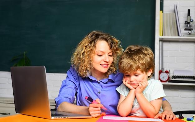 Insegnante felice che aiuta l'alunno all'istruzione elementare nella scuola elementare imparando la matematica e