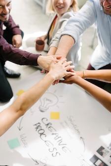 Squadra felice che unisce le mani per il successo