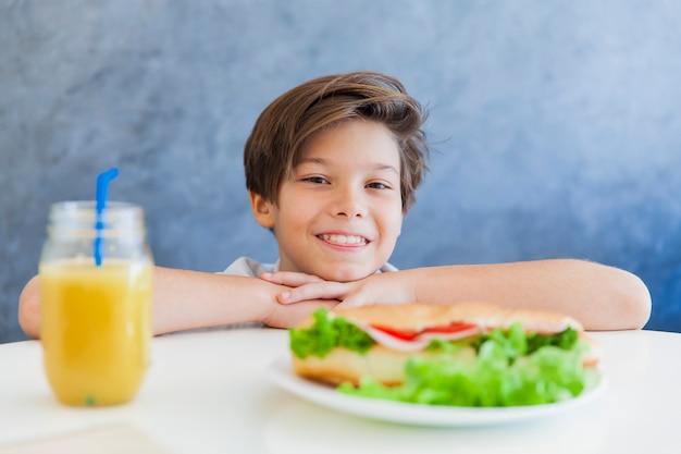Ragazzo teenager felice che mangia prima colazione a casa